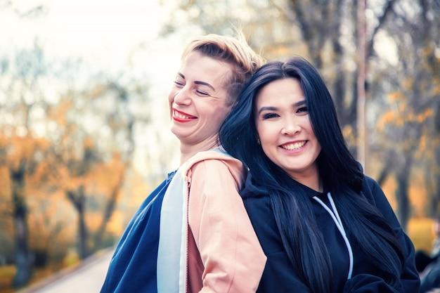 Dwie młode piękne kobiety, azjatycka i europejska, stoją plecami w zachodzącym słońcu, koncepcja dnia przyjaźni