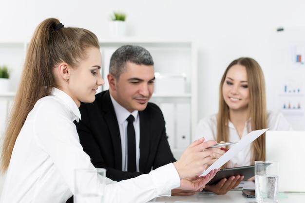 Dwie młode piękne kobiety biznesu konsultują się z kolegą. partnerzy omawiający dokumenty i pomysły