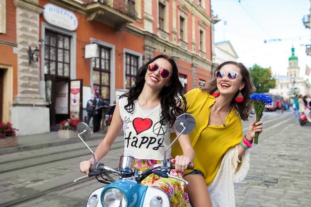 Dwie młode piękne kobiety hipster, jazda na motocyklu ulicy miasta