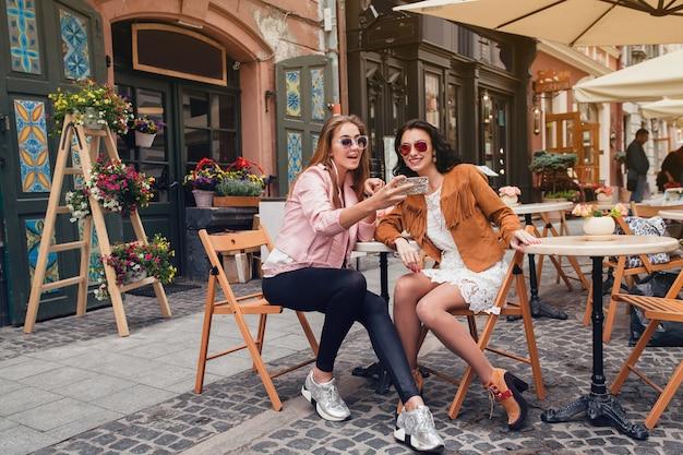 Dwie młode piękne kobiety hipster siedzi w kawiarni