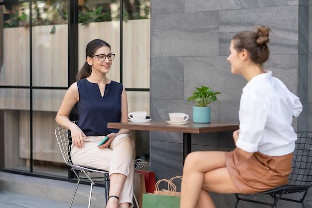 Dwie młode piękne kobiety przyjaciele rozmawiają i siedzą na tarasie kawiarni na zewnątrz