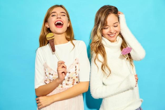 Dwie młode piękne kobiety śpiewające z rekwizytami fałszywy mikrofon. modne kobiety w codziennych letnich ubraniach. pozytywne kobiece emocje mimika język ciała z dużymi ustami. śmieszne modele na niebieskim tle
