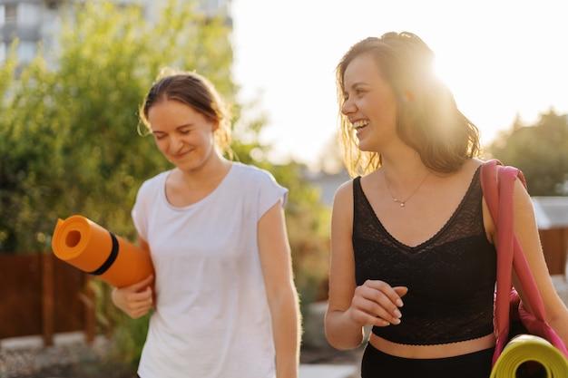 Dwie młode piękne kobiety w odzieży sportowej zamierzają uprawiać sport, gimnastykę, jogę