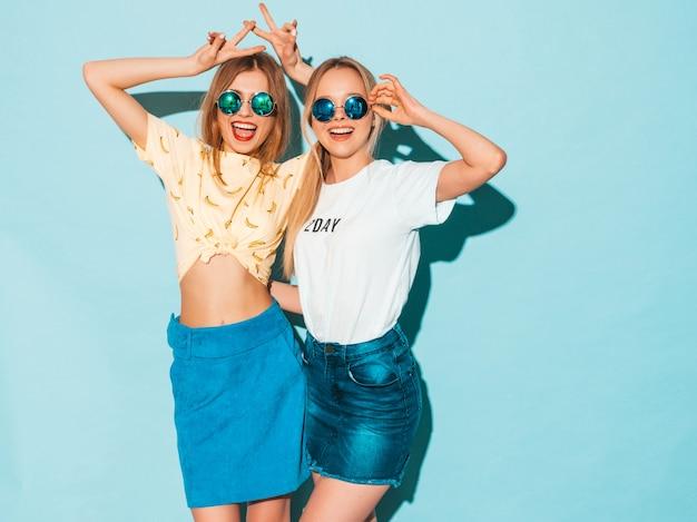 Dwie młode piękne uśmiechnięte blond hipster dziewczyny w modne letnie dżinsy spódnice ubrania.