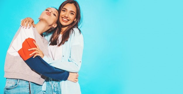 Dwie młode piękne uśmiechnięte blond hipster dziewczyny w modne letnie kolorowe ubrania t-shirt. seksowne beztroskie kobiety pozuje blisko błękit ściany. pozytywne modele świetnie się bawią i kaczą twarz