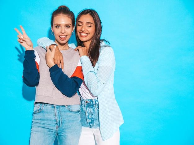 Dwie młode piękne uśmiechnięte blond hipster dziewczyny w modne letnie kolorowe ubrania t-shirt. seksowne beztroskie kobiety pozuje blisko błękit ściany. pozytywne modele zabawy