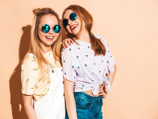 Dwie młode piękne uśmiechnięte blond hipster dziewczyny w modne letnie kolorowe ubrania t-shirt.