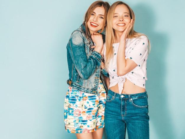 Dwie młode piękne uśmiechnięte blond hipster dziewczyny w modne letnie kolorowe ubrania.