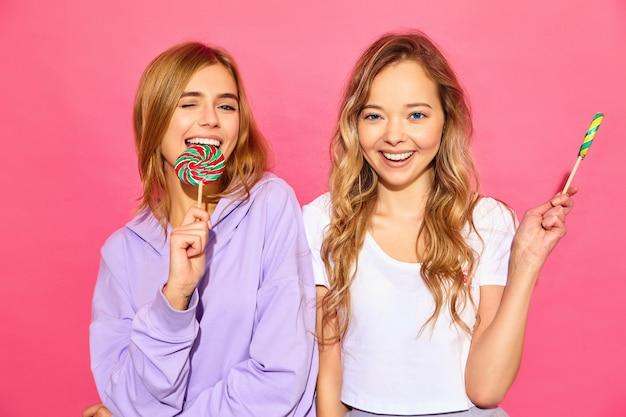Dwie młode piękne uśmiechnięte blond hipster kobiety w modne letnie ubrania. beztroskie gorące kobiety pozuje blisko menchii ściany. pozytywne śmieszne modele z lollipop