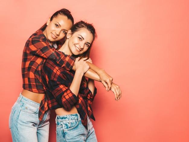 Dwie młode piękne uśmiechnięte brunetki hipster dziewczyny w modnej podobnej kraciastej koszuli i dżinsach. seksowne beztroskie kobiety pozujące w pobliżu różowej ściany w studio. pozytywne modele zabawy