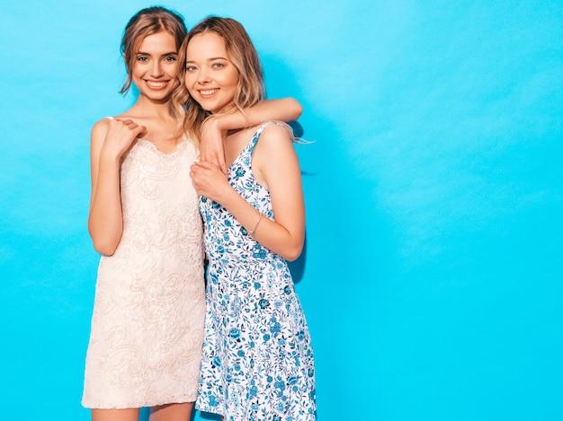 Dwie młode piękne uśmiechnięte dziewczyny hipster w modne letnie sukienki na co dzień. seksowne beztroskie kobiety pozuje blisko błękit ściany. zabawy i przytulania. modele pokazują dobre relacje. kobieta bez makijażu
