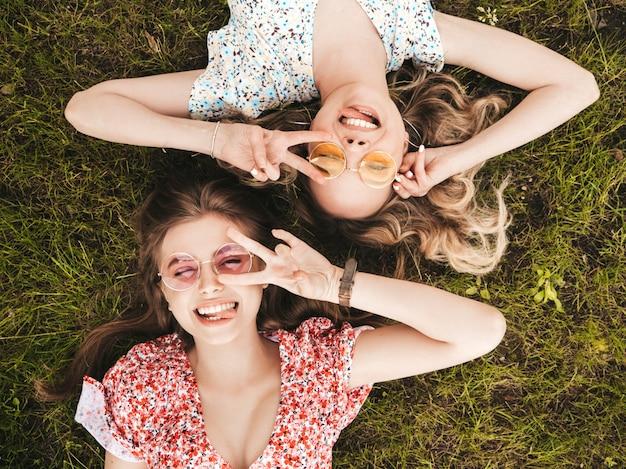 Dwie młode piękne uśmiechnięte dziewczyny hipster w modne letnie sukienki. seksowne beztroskie kobiety leżące na zielonej trawie w okularach przeciwsłonecznych. pozytywne modele zabawy. widok z góry. pokazują znak pokoju