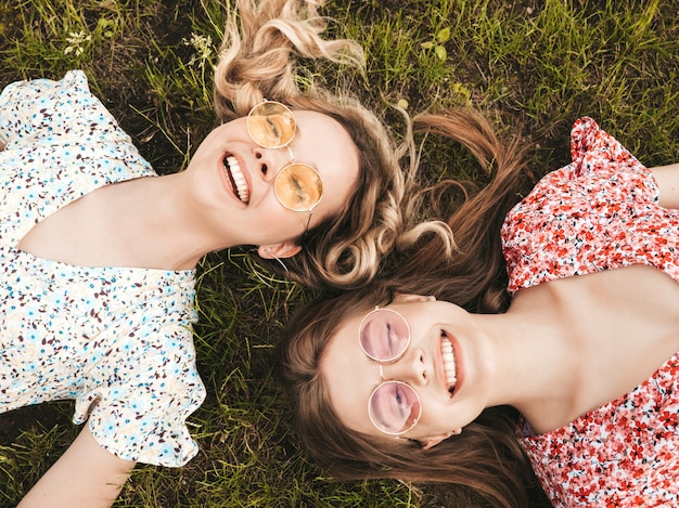 Dwie młode piękne uśmiechnięte dziewczyny hipster w modne letnie sukienki. seksowne beztroskie kobiety leżące na zielonej trawie w okularach przeciwsłonecznych. pozytywne modele zabawy. widok z góry