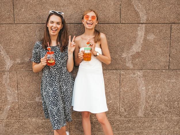 Dwie młode piękne uśmiechnięte dziewczyny hipster w modne letnie sukienki.