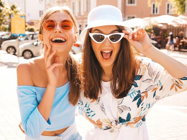 Dwie młode piękne uśmiechnięte dziewczyny hipster w modne letnie ubrania i kapelusz panama.