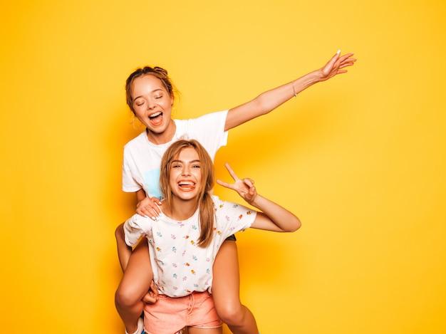 Dwie młode piękne uśmiechnięte dziewczyny hipster w modne letnie ubrania. seksowne beztroskie kobiety pozuje blisko kolor żółty ściany. modelu obsiadanie na przyjaciółki plecy i podnosić ręki