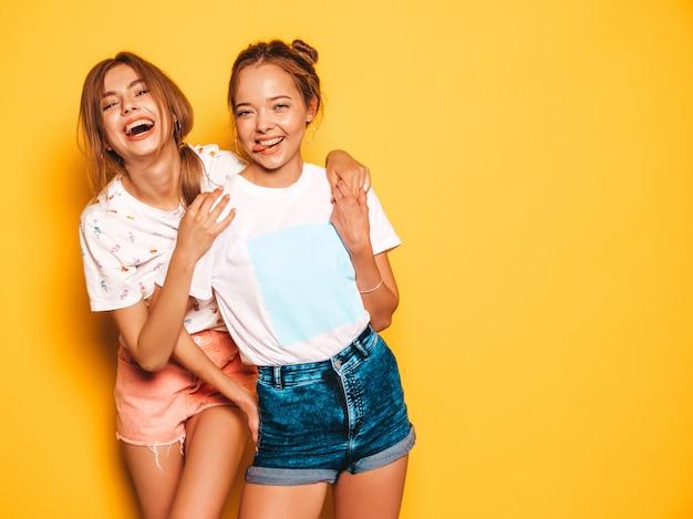 Dwie młode piękne uśmiechnięte dziewczyny hipster w modne letnie ubrania. seksowne beztroskie kobiety pozuje blisko kolor żółty ściany. pozytywne modele wariują i dobrze się bawią