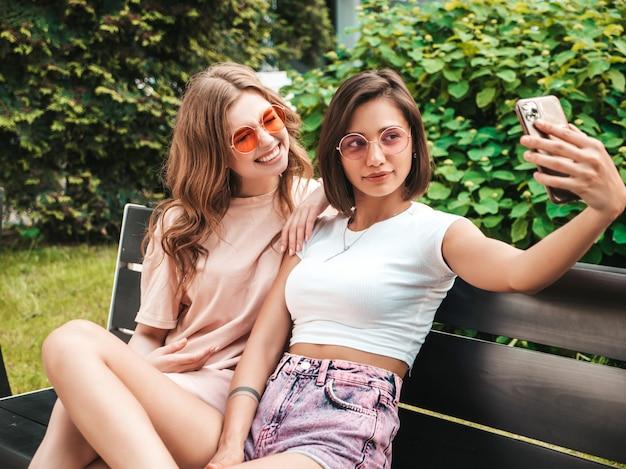 Dwie młode piękne uśmiechnięte dziewczyny hipster w modne letnie ubrania. seksowne beztroskie kobiety siedzą na ławce na ulicy w okularach przeciwsłonecznych. robią autoportrety na smartfonie
