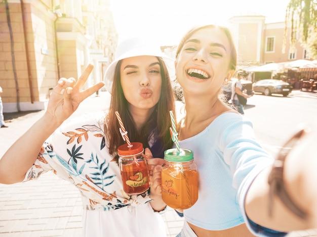 Dwie młode piękne uśmiechnięte dziewczyny hipster w modne letnie ubrania