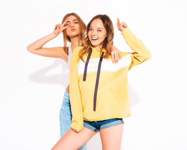 Dwie młode piękne uśmiechnięte dziewczyny w modne letnie dżinsy i żółtą bluzę z kapturem. beztroskie kobiety. pozytywne modele