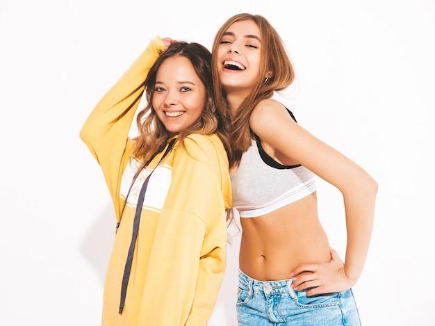 Dwie młode piękne uśmiechnięte dziewczyny w modne letnie dżinsy ubrania. seksowne beztroskie kobiety. pozytywne modele