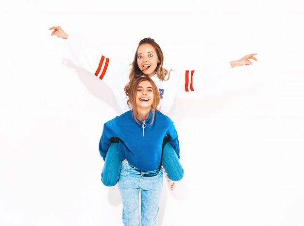 Dwie młode piękne uśmiechnięte dziewczyny w modne letnie ubrania. beztroskie kobiety. pozytywny model siedzący na plecach przyjaciółki i podnoszący ręce