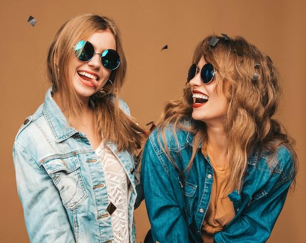 Dwie młode piękne uśmiechnięte dziewczyny w modne letnie ubrania i okulary przeciwsłoneczne. seksowny beztroski kobiet pozować. pozytywne modele krzyczące pod konfetti