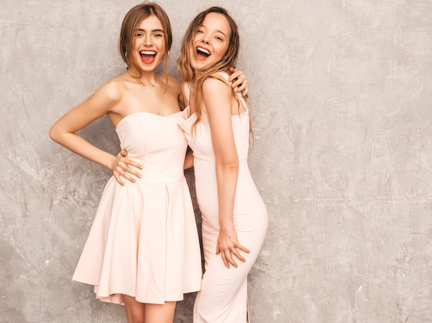Dwie młode piękne uśmiechnięte dziewczyny w modnych letnich jasnoróżowych sukienkach. seksowny beztroski kobiet pozować. pozytywne modele zabawy