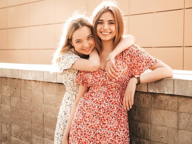 Dwie młode piękne uśmiechnięte hipster dziewczyny w modne letnie sukienki. seksowne beztroskie kobiety pozowanie na tle ulicy. pozytywne modele zabawy i szaleństwa