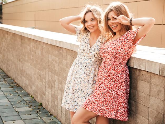 Dwie młode piękne uśmiechnięte hipster dziewczyny w modne letnie sukienki. seksowne beztroskie kobiety pozowanie na tle ulicy. pozytywne modele zabawy i znak pokoju