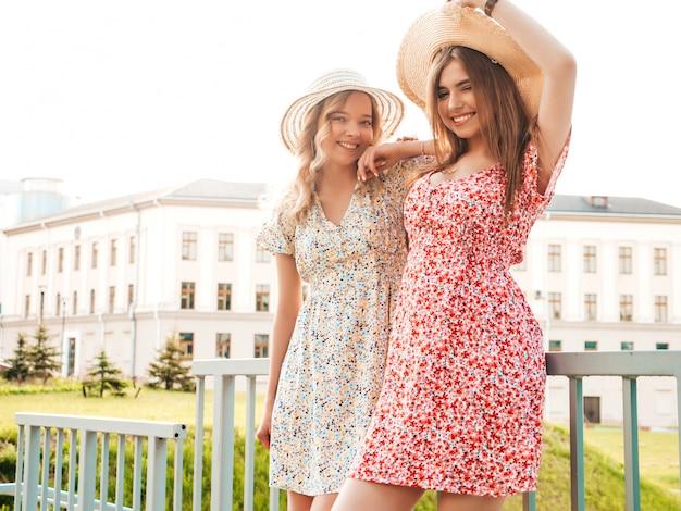 Dwie młode piękne uśmiechnięte hipster dziewczyny w modne letnie sukienki. seksowne beztroskie kobiety pozowanie na tle ulicy w kapeluszach. pozytywne modele zabawy i przytulania