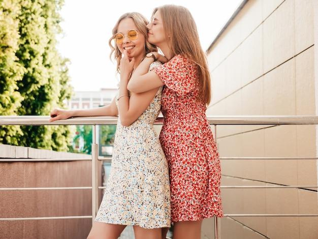Dwie młode piękne uśmiechnięte hipster dziewczyny w modne letnie sukienki. seksowne beztroskie kobiety pozowanie na tle ulicy w okulary przeciwsłoneczne. pozytywne modele zabawy i szaleństwa
