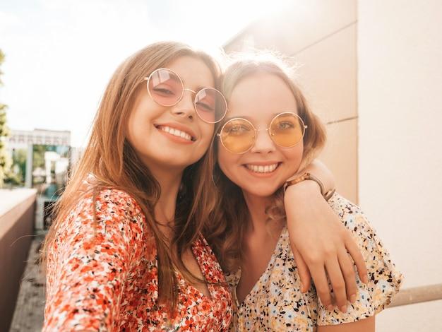Dwie młode piękne uśmiechnięte hipster dziewczyny w modne letnie sukienki. seksowne beztroskie kobiety pozowanie na tle ulicy w okulary przeciwsłoneczne. robią selfie autoportrety na smartfonie o zachodzie słońca
