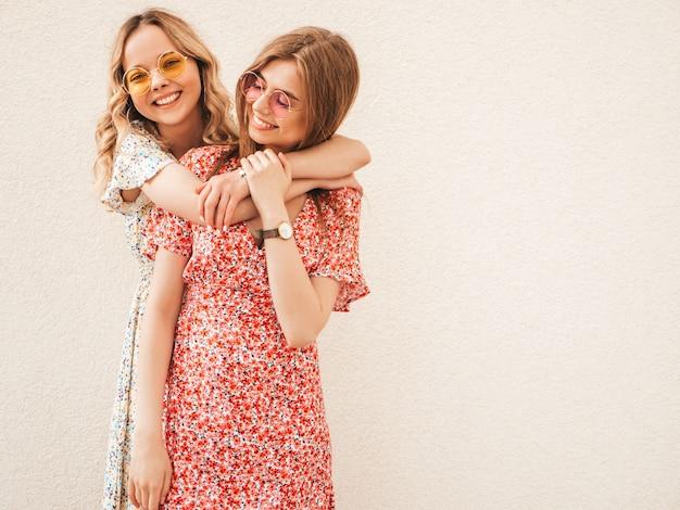 Dwie młode piękne uśmiechnięte hipster dziewczyny w modne letnie sukienki. seksowne beztroskie kobiety pozowanie na ulicy w pobliżu ściany w okulary przeciwsłoneczne. pozytywne modele zabawy i szaleństwa