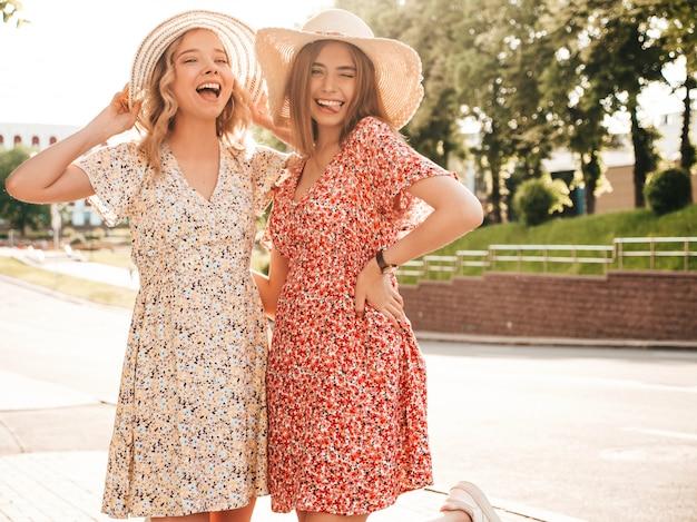 Dwie młode piękne uśmiechnięte hipster dziewczyny w modne letnie sukienki. seksowne beztroskie kobiety pozuje na ulicznym tle w kapeluszach przy zmierzchem. pozytywne modele zabawy i przytulania