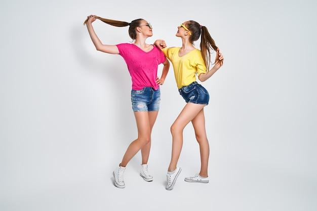 Dwie młode piękne uśmiechnięte hipster dziewczyny w modne letnie ubrania beztroskie kobiety pozowanie na białym tle w studio