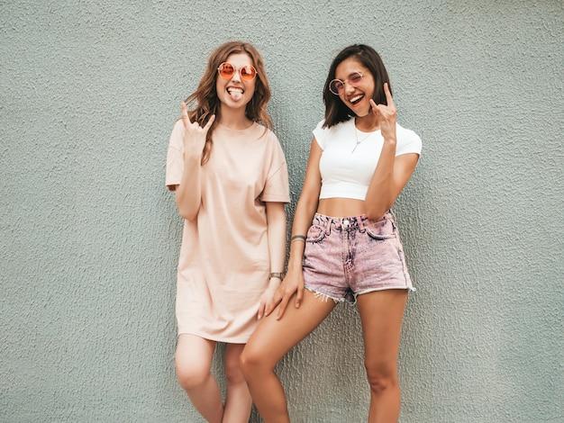 Dwie młode piękne uśmiechnięte hipster dziewczyny w modne letnie ubrania. seksowne beztroskie kobiety pozowanie na ulicy w pobliżu ściany w okulary przeciwsłoneczne. pozytywne modele świetnie się bawią i pokazują znak rock and rolla