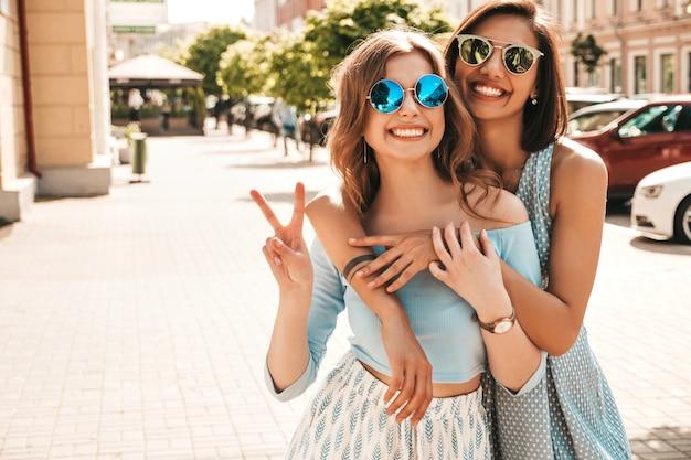 Dwie młode piękne uśmiechnięte hipster dziewczyny w modne letnie ubrania. seksowne beztroskie kobiety pozuje na ulicznym tle w okularach przeciwsłonecznych. pozytywne modele zabawy i przytulania. pokazując znak pokoju