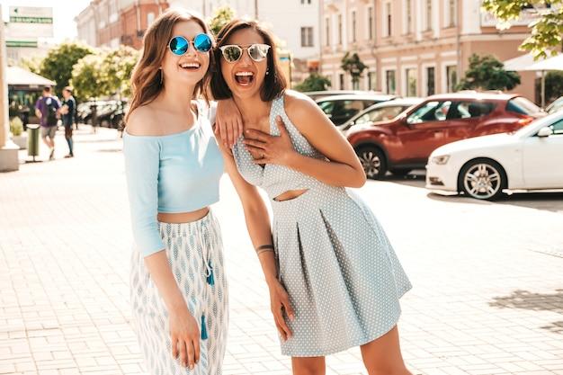 Dwie młode piękne uśmiechnięte hipster dziewczyny w modne letnie ubrania. seksowne beztroskie kobiety pozuje na ulicznym tle w okularach przeciwsłonecznych. pozytywne modele zabawy i przytulania