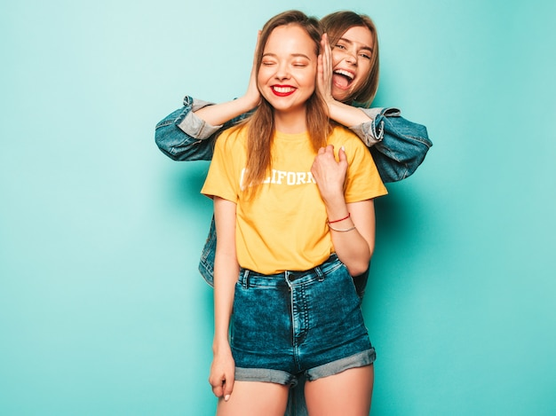 Dwie młode piękne uśmiechnięte hipster dziewczyny w modne letnie żółte koszulki i kurtkę jeansową. seksowne beztroskie kobiety pozuje blisko błękit ściany. modne i pozytywne modele zabawy