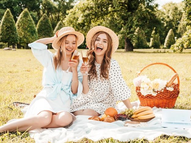 Dwie młode piękne uśmiechnięte hipster dziewczyny w modnej letniej sukience i kapeluszach. beztroskie kobiety co piknik na zewnątrz.
