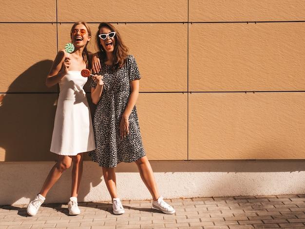 Dwie młode piękne uśmiechnięte hipster dziewczyny w modnej letniej sukience.