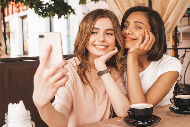 Dwie młode piękne uśmiechnięte hipster dziewczyny w modnych letnich ubraniach. beztroskie kobiety na czacie w kawiarni na werandzie i picie kawy. pozytywne modele zabawy i selfie na smartfonie