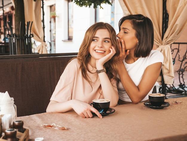 Dwie młode piękne uśmiechnięte hipster dziewczyny w modnych letnich ubraniach. beztroskie kobiety na czacie w kawiarni na werandzie i pijące kawę. pozytywny model dzieli sekret z koleżanką