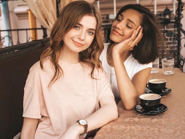 Dwie młode piękne uśmiechnięte hipster dziewczyny w modnych letnich ubraniach. beztroskie kobiety na czacie w werandzie na tarasie kawiarni i picia kawy. pozytywne modele zabawy i komunikacji