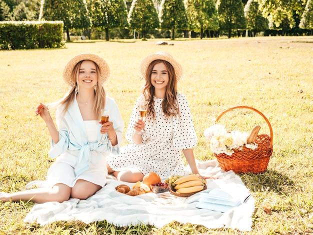 Dwie młode piękne uśmiechnięte hipster kobieta w letniej sukience i kapeluszach. beztroskie kobiety co piknik na zewnątrz.