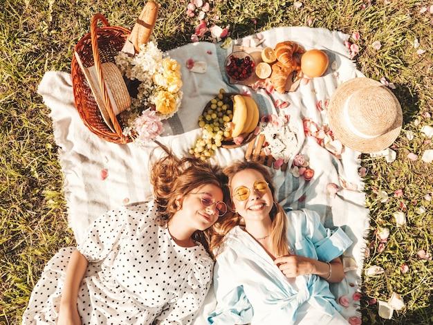 Dwie młode piękne uśmiechnięte hipster kobieta w modnej letniej sukience i kapeluszach. beztroskie kobiety co piknik na zewnątrz.