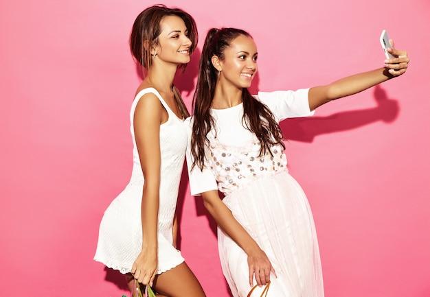 Dwie młode piękne uśmiechnięte hipster kobiety w modne letnie ubrania. seksowne beztroskie kobiety pozuje blisko błękit ściany. pozytywne modele co selfie na telefon