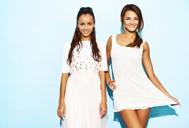 Dwie młode piękne uśmiechnięte hipster kobiety w modne letnie ubrania. seksowne beztroskie kobiety pozuje blisko błękit ściany. pozytywne modele