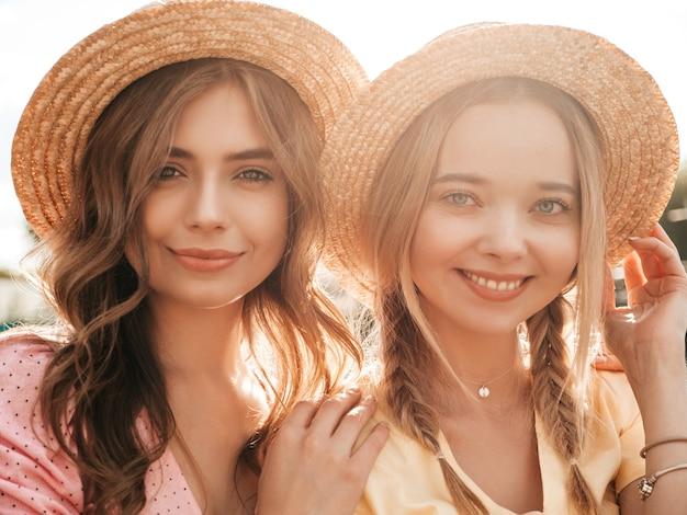 Dwie młode piękne uśmiechnięte hipster kobiety w modnej letniej sukience